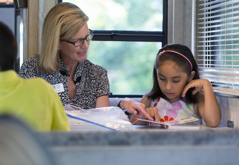 Volunteer Cindy Johanson reads with 7-year-old Tomasa at a Read and Feed mobile classroom.