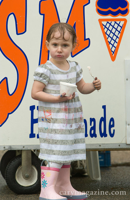 Rain-soaked and crayon-stained, 2-year-old Riley Colon experiences what appears to be an ice-cream headache while chomping on a chilly treat. The youngster was one of hundreds who braved the wet weather March 24, 2012 at the Town of Cary inaugural Wheels on Academy Car and Motorcycle Show.