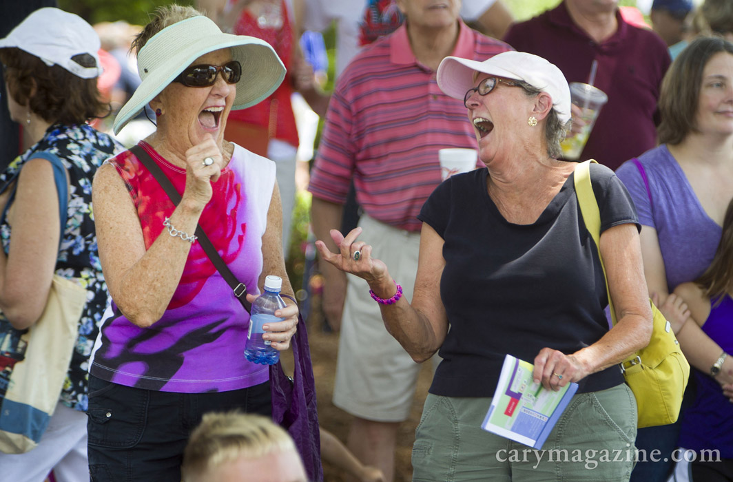 Chapel Hill resident Mary Garren's rocking dance moves (left) has Cary neighbor Prudy Miller in stitches during a live performance by cover band Big Love at Cary's Lazy Daze Arts and Crafts Festival, 2015.