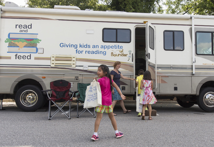 Volunteer and Program Director Heather Cross welcomes kids to the Read and Feed mobile unit parked at First United Methodist Church in Cary.