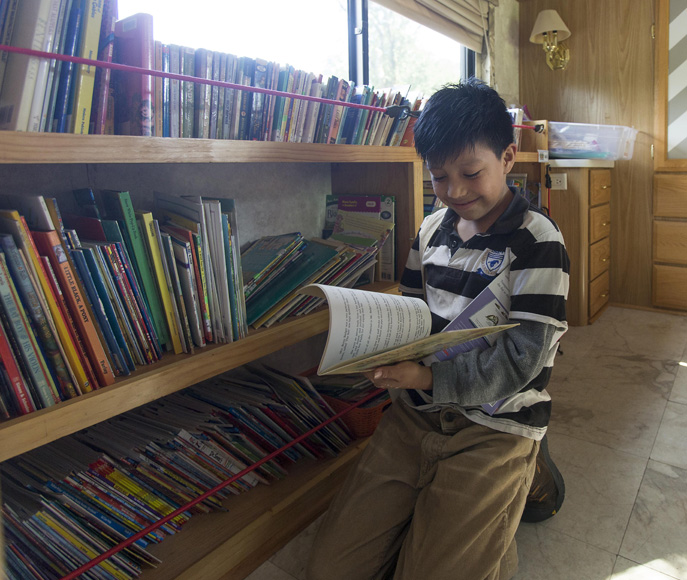 Nine-year-old Dain Barolotn picks out a book to read. Participants are allowed to take home books to read on their own.