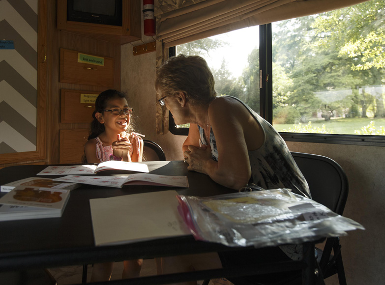 Nine-year-old Yamileth Melgares works with volunteer Sharon Bollini in the Read and Feed bus.