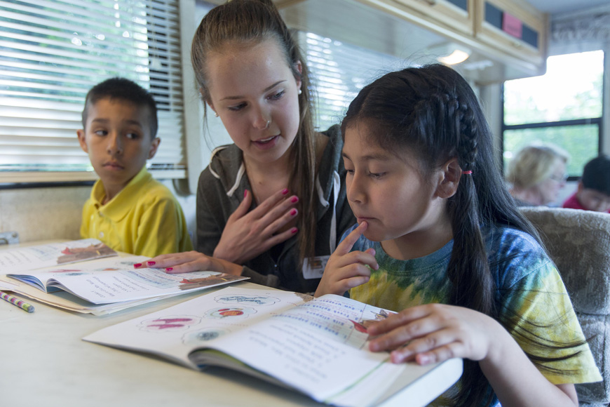 Green Hope High School junior Gigi Juras helps Evelyn Morales-Morales with her reading as Ulises Maya-Mederos (left) reads on his own. Both 8-year-olds frequent the Read and Feed bus.
