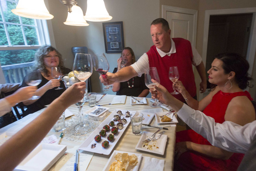 Host Barry Daniels toasts his guests as Marijane Strohbusch, left, Alicia Lehmkuhl, center, and Amy Barfield raise their glasses.