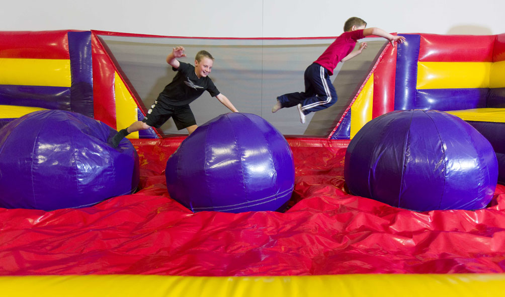Holly Springs brothers Michael and Alex Duncan, ages 11 and 7, test their agility on an inflatable obstacle at Bounce U in Apex.
