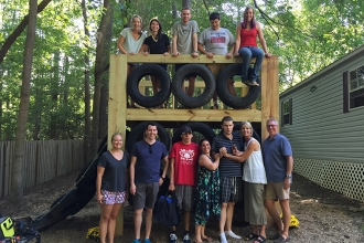 """Housing is the biggest problem in autism right now,"" says Hannah Ellis, who launched Living With Autism and its group home on behalf of her son Sam. A play structure for residents of the home was designed and built by students in the AIAS N.C. State University Freedom by Design Program. Pictured from top left are AIAS FBD team members Sam Lackey, Allison Menius, Alex Buck, group home resident Jake, and Gabby Seider. Bottom, Kelsey Morrison, Scott Needham, resident Robby, group home manager Cathy Newton, Sam, and Hannah and Nick Ellis."