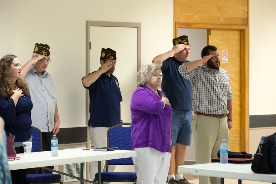 "Post and auxiliary members salute the American flag at a recent meeting of Cary VFW Post 7383. ""We all have the same desire to work supporting veterans, and volunteering where we can in service and camaraderie,"" says Auxiliary Senior Vice President Donna Wright."