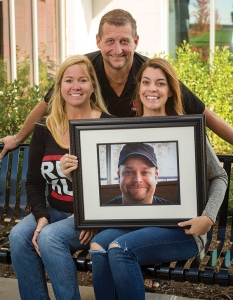 Robert Royster, standing, Ashley Royster, left, and Amy Pilz, holding a photo of the late Ryan Pilz, have grown Ruckus Pizza, Pasta & Spirits from a bar 18 years ago into a family-friendly restaurant with four locations.