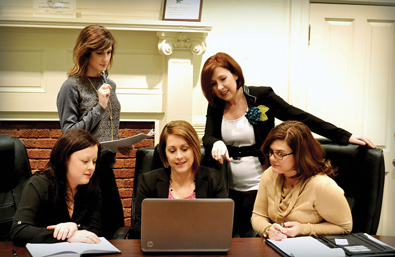 Jennibeth Brackett, seated behind computer, and Missy Gower, standing at right, founded Career Crafters for You to coach men and women returning to the workforce after a gap. They are with Leann Jackson, Meghan Taylor and Catherine Shireman.