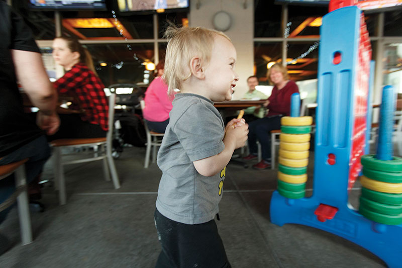 Trevor Skelton, 18 months, races around with french fry in hand on the patio at Ruckus Pizza, Pasta & Spirits in Morrisville, at Park West Village.