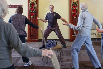 """Howie Shareff leads participants through a series of gentle moves, both seated and standing. """"Yoga is a physical, mental and spiritual practice that can be achieved by anyone to some degree,"""" he says."""
