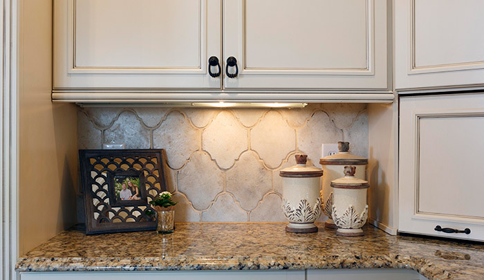 """Look closely for some of the best details in this kitchen refresh: The cabinets, formerly a buttery yellow, were refinished and glazed, and hardware updated from silver to oil-rubbed bronze. The backsplash, updated with handmade tile from California, """"spoke to me,"""" says homeowner Gretchen Cooling. Designer Vicky Serany notes that the tile is neutral, but has great texture and adds visual interest."""