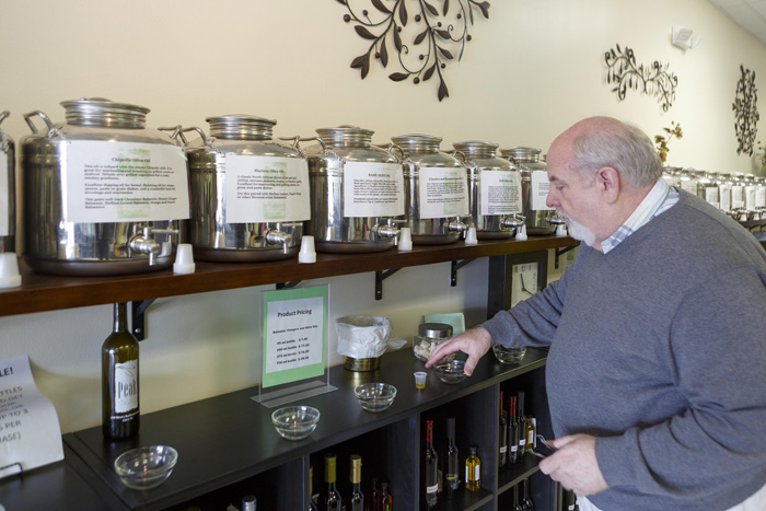 Craig Gaither, store manager at Peak Olive Oil Company in Cary, encourages customers to sample their wide variety of fresh olive oils.