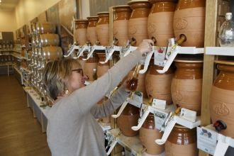 At VomFass, Kathleen Drew fills a bottle of oil. Customers can bring their own containers, taste the various oils, and buy enough to use in three or four months. Staff also encourages customers to reuse and refill any bottles they buy at the store.