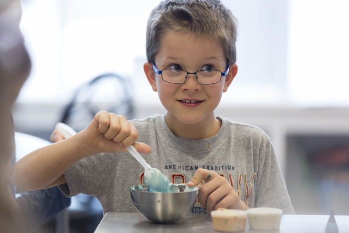"Andrew Earl, 8, likes to cook eggs and bacon at home, but doesn't like to share the kitchen with his brother, Alex. He enjoyed the day of baking, especially the morning project — apple fritters. ""They were delicious,"" he said."