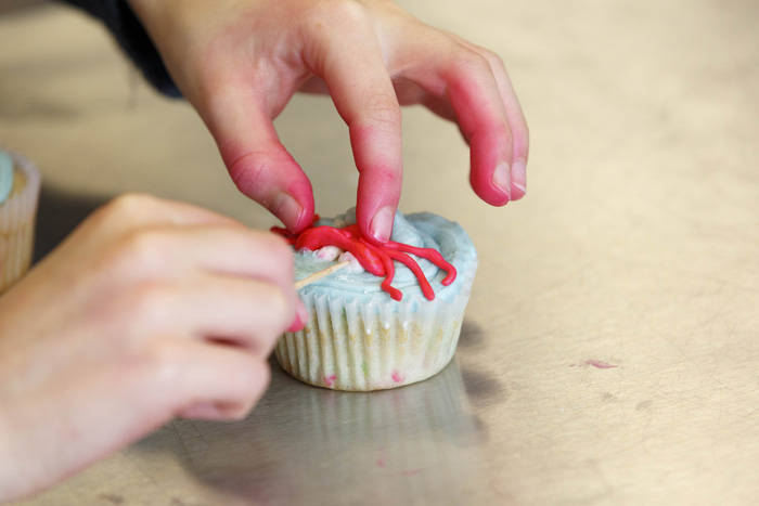 "A crab-topped cupcake gets some finishing touches during the final activity of the day-long workshop — a competition inspired by the Food Network program ""Cupcake Wars."""