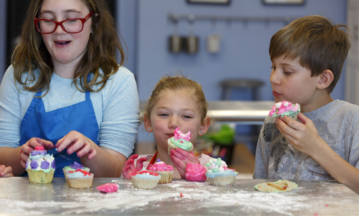 "Kyra Pettibone, left, Dylan Salzman, center, and Alex Earl dig into the cupcakes they've decorated. ""I like making cakes and cupcakes — I like icing them,"" said Kyra, who received a set of icing tubes for her last birthday."