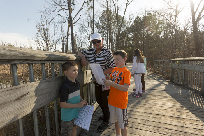 Marlene Bush, of Wake Forest, pauses on the bridge over Beaver Creek in Apex with her grand-sons Aiden, 7, and Alex Erling. Bush spends one weekend a month with the boys, and has enjoyed exploring area parks with them as they complete the Wake County Junior Park Naturalists program.