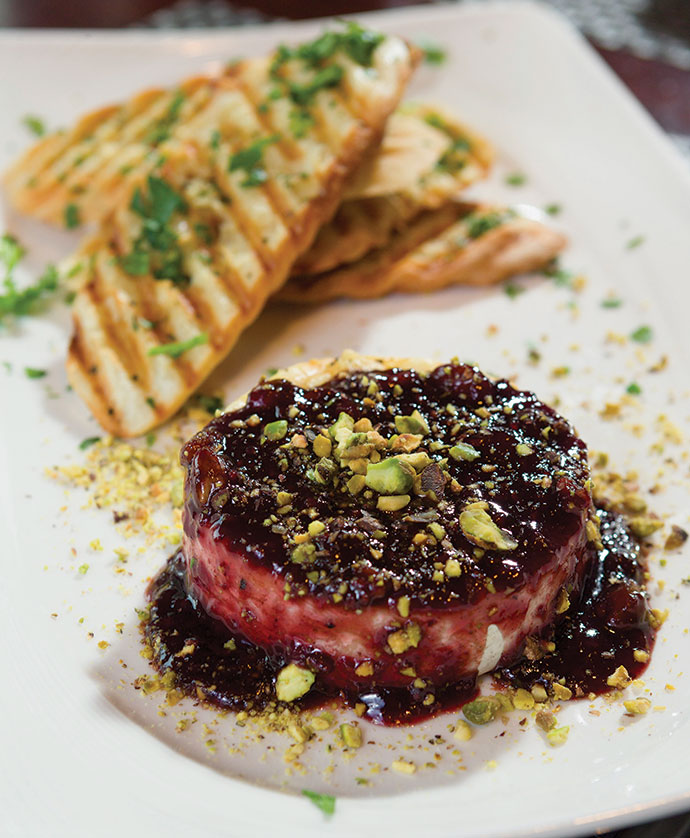 Grilled brie appetizer is served with a port wine raspberry reduction, toasted pistachio nuts and grilled toast points at Academy Street Bistro.