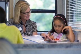 Read and Feed is the local nonprofit selected to benefit from this weekend's Triangle's Got Talent, hosted by the Cary Teen Council. Here, Read and Feed volunteer Cindy Johanson reads with Tomasa in the organization's mobile classroom.