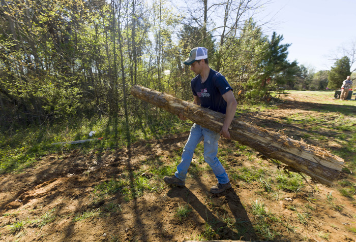 "Farm manager Zeke Overbaugh helps build deer fencing at the farm. ""I'm excited about this project because it means it's becoming normal for towns and citizens to think about urban farming,"" he says."