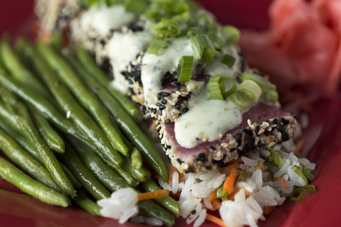 Sesame encrusted ahi tuna is served with jasmine rice and a vegetable. It is finished with cilantro wasabi cream sauce.