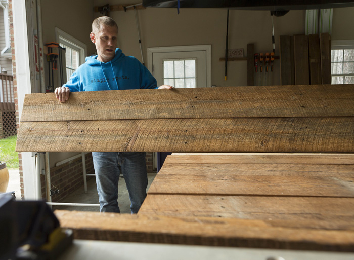 "Jeff Thompson of Simple Roots Décor arranges reclaimed boards to create a rustic barn door to be used inside a client's home. The wood came from a Lillington tobacco barn, built in 1903. ""Barn doors are really big now,"" he says, but the original barn doors are usually too weathered to be salvaged."