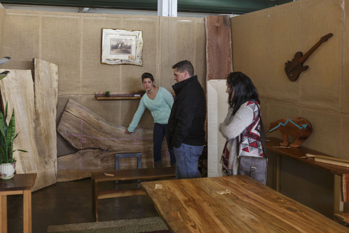 Live Edge Wood Design's Liz ___ shows furniture to Morrisville couple Pet McDaniel and Karolina Gabbrielli at the NC State Fairgrounds booth.