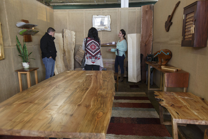 Liz Ferebee talks to Pet McDaniel and Karolina Gabbrielli, of Morrisville, at the Live Edge Wood Designs retail space at the State Fairgrounds. Open on weekends, the booth displays finished pieces and wood slabs that can be made into custom creations.
