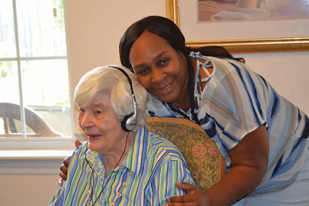 Music is making a big impact in the life of Beverly Norenton, seated, and others with memory impairment, through the Music & Memory program provided by the Holly Springs and Apex Sunrise Rotary Clubs to six local senior communities including Carillon Assisted Living in Fuquay-Varina. Assisting Norenton is Carillon staffer Shawanda Jones.