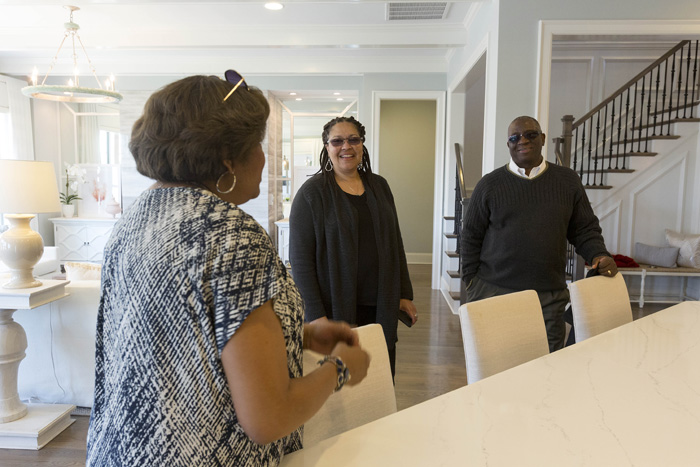 Real estate agent Peggy Dixon leads Joscie and Chris Barnes on a tour of the model home that their under-construction house is based on, featuring the amenities many house hunters are looking for, including granite countertops, hardwood floors, and a first-floor master.