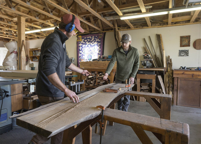 "Quinn Ferebee, left, and Doug Boytos of Live Edge Wood Designs get ready to trim a slab that will become a dining room table. The pair works with the tree's natural shape in their designs. ""The slabs dictate what can be made from them,"" says Boytos."