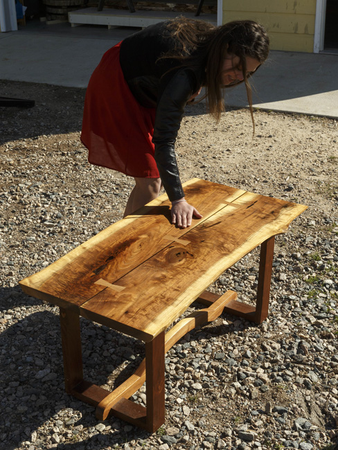 Liz Ferebee shows off her coffee table, a gift from her husband, Quinn, who made it from black walnut he inherited from his great-grandfather.
