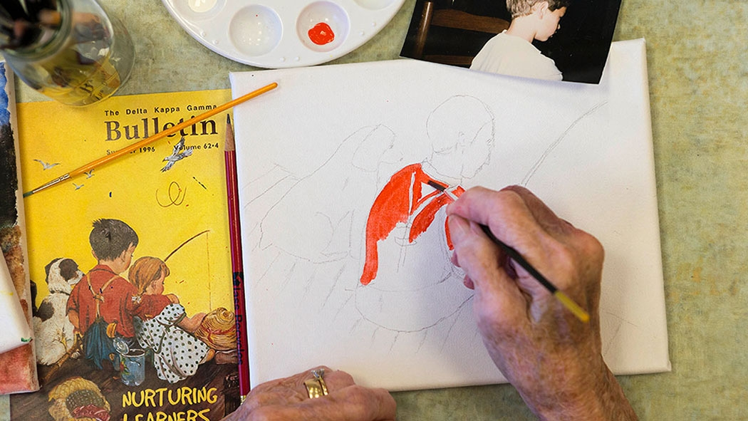 Working from a photo, Jeanette Brooks paints a portrait of her grandson during an arts class at Waltonwood in Cary. Experts say seniors benefit in numerous ways from hands-on participation in the arts.