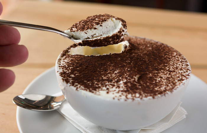 House-made tiramisu comes in a bowl dusted with cocoa powder.