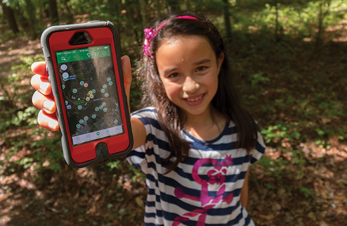 Delaney Feung searches for caches using the geocache app on her father's phone.