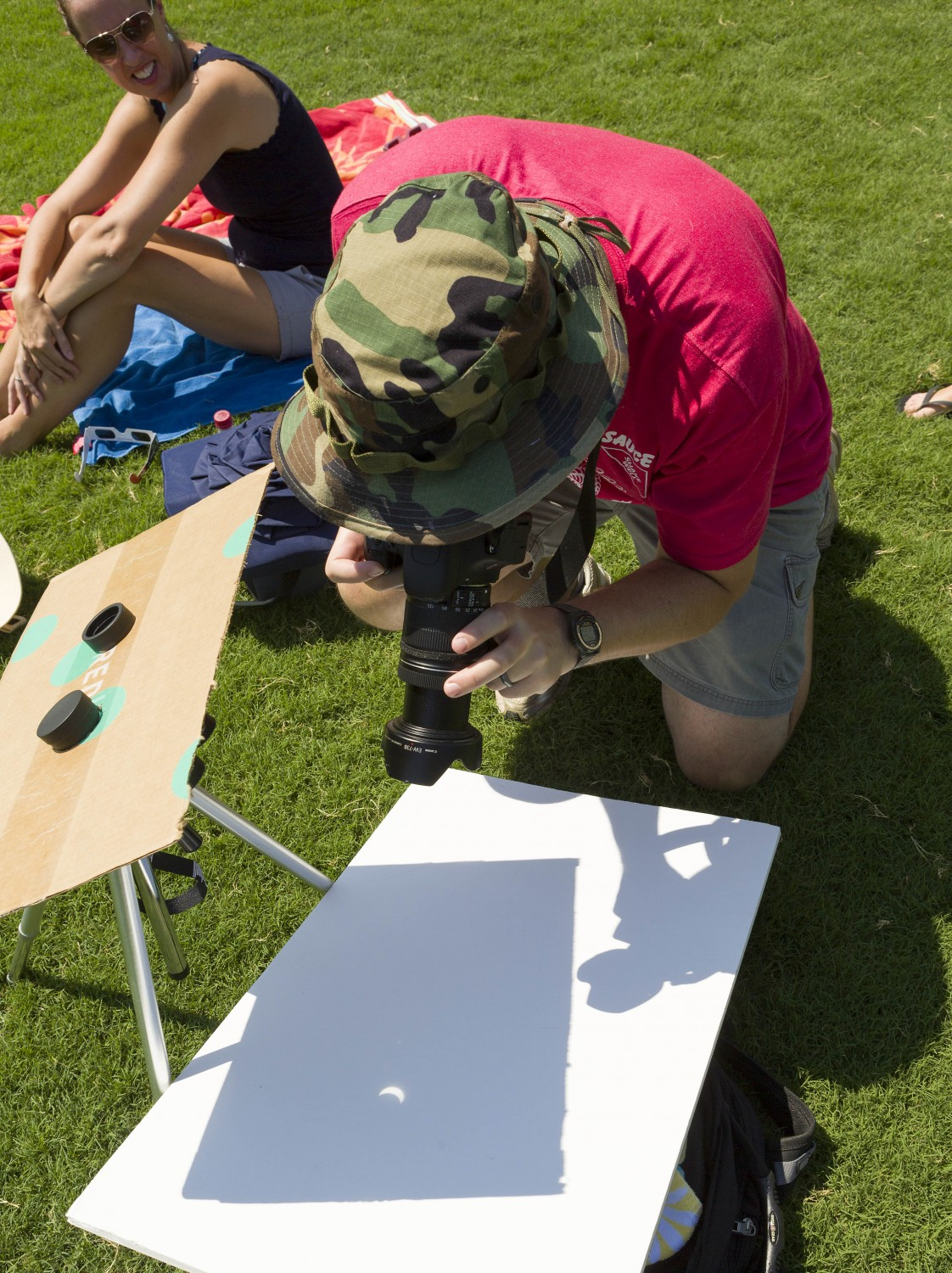 T.J. Hill of Cary focuses on the solar eclipse as projected and magnified by binoculars on a piece of foam core. Hill tried out his homemade pinhole camera at North Cary Park, where he and his family, including wife Jennifer, joined others for the historic event.