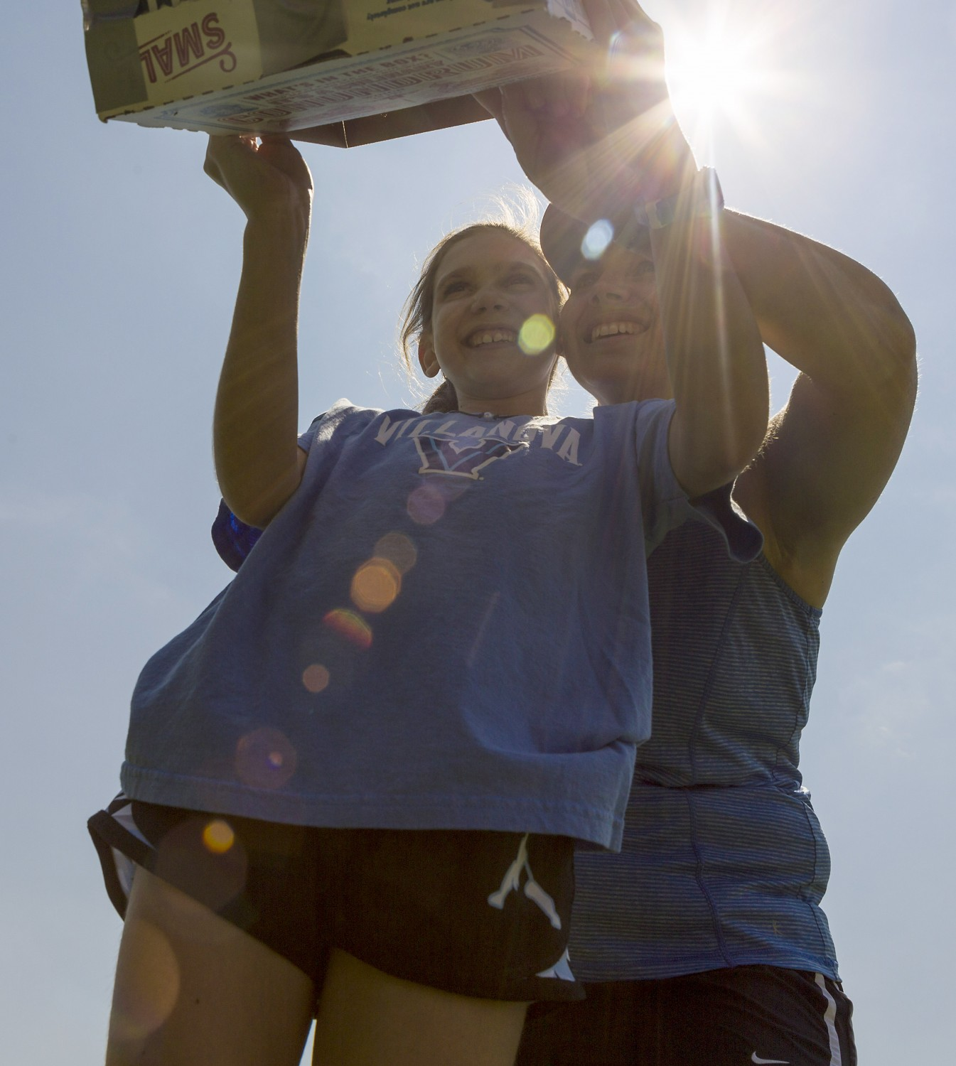 Erin Curtis and mom Kelly view the eclipse through a box they converted into a pinhole camera.
