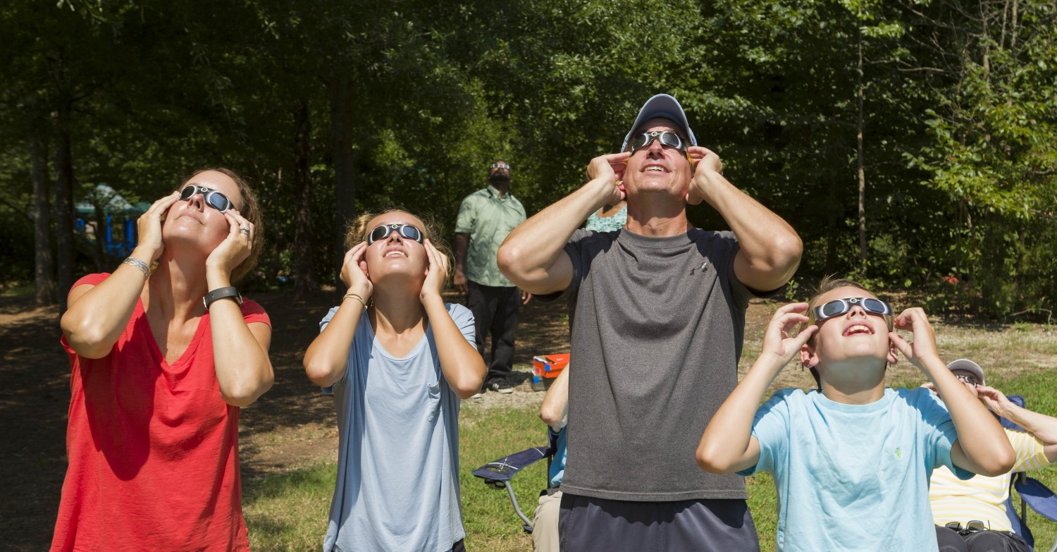Many people donned their eclipse glasses at North Cary Park Aug. 21 to witness the solar eclipse. From left, Cary family Kristin Sierenaler and Kara, Ron and Nick Van Arnam.