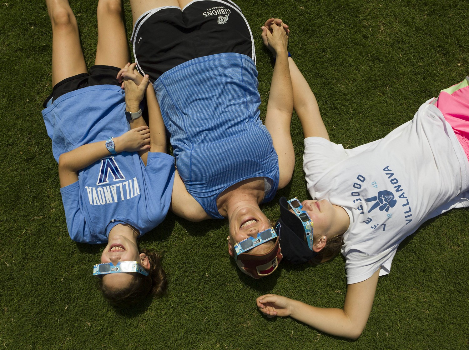 Kelly Curtis of Cary, center, lies on the grass with daughters Erin, left, and Emily, ages 11 and 17, during the solar eclipse.