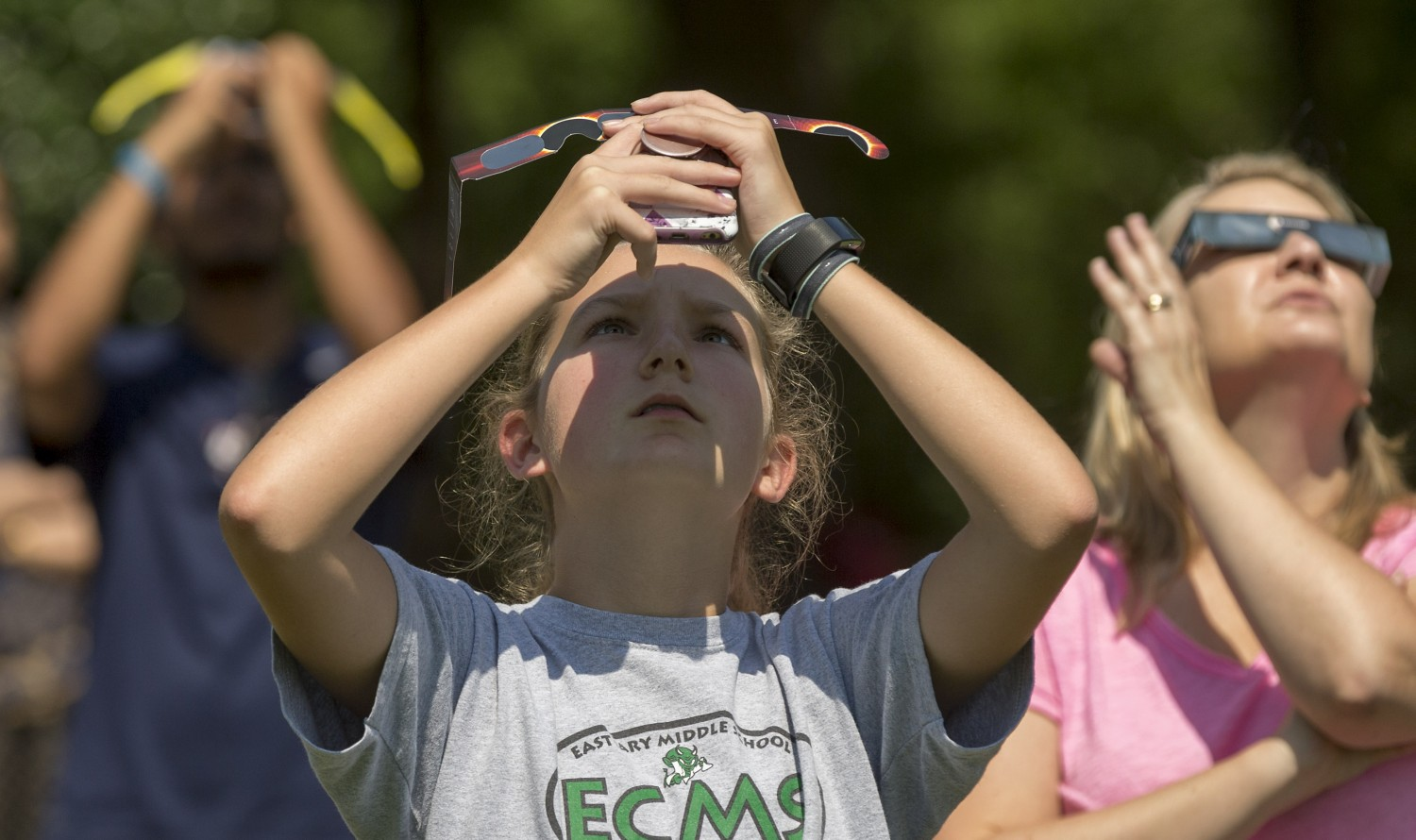A viewer covers the lens of her cell phone with eclipse glasses in an attempt to take a photo of the eclipse.