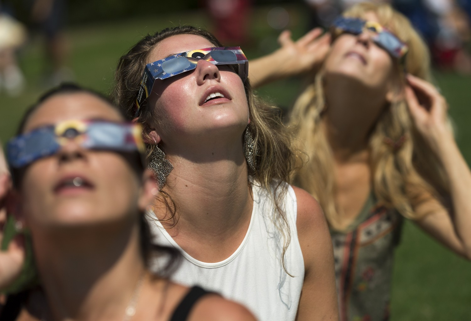 Leah Brown, center, enjoys the solar eclipse at North Raleigh Park.