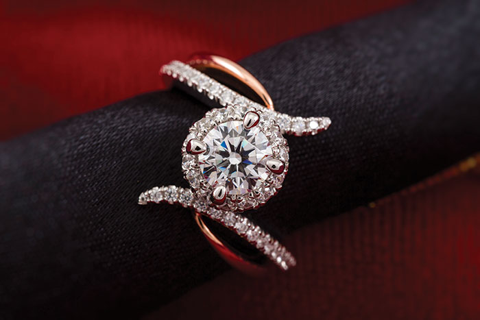 This round halo engagement ring from Anfesa's Jewelers features 14K white and rose gold.