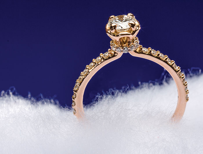 This 14K rose gold engagement ring from J.M. Edwards has a large center stone and smaller diamonds on the band.
