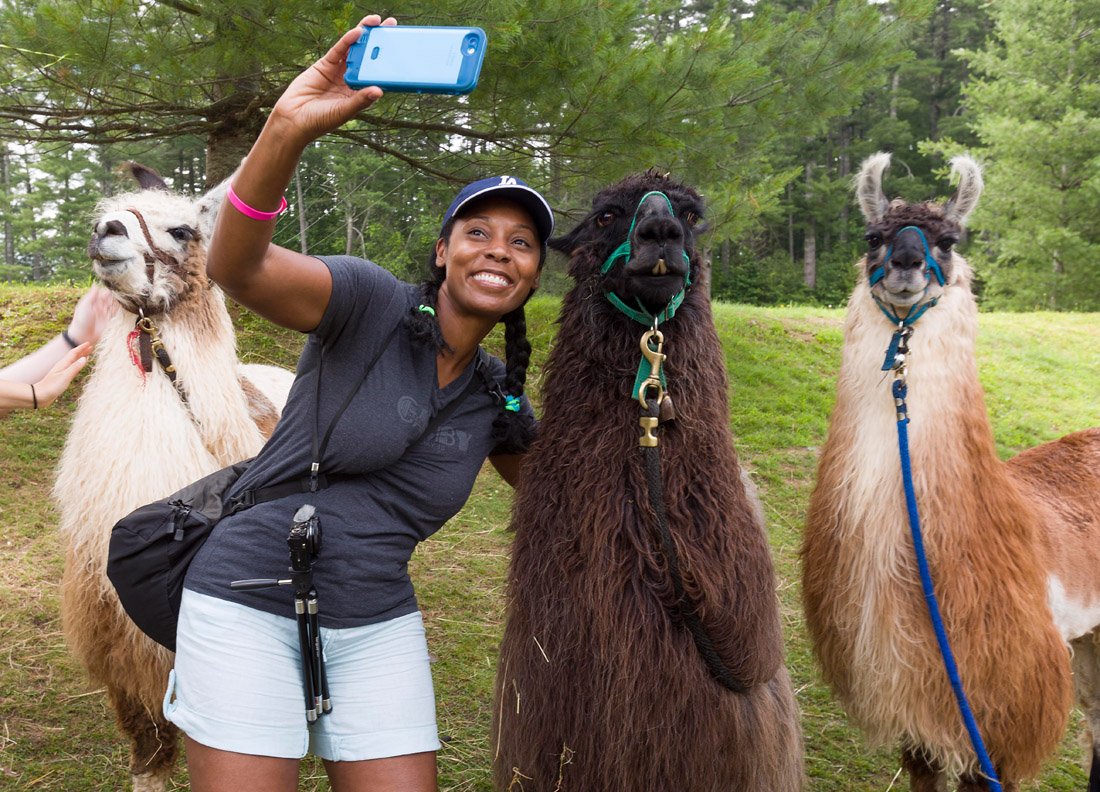 Atlanta resident Dayvee Sutton poses with some llamas at the High Hampton Inn in Cashiers, where guests of all ages can hike with a pack of llamas on a mountain lake trail.