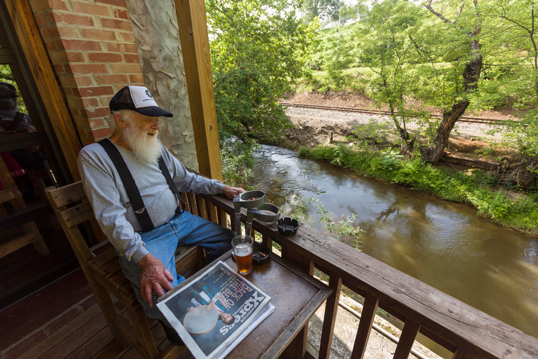Sylva local Don Turton enjoys a pint on a covered patio overlooking Scott Creek at Innovation Brewing. Sylva's Main Street hosts four breweries in an easily walkable, scenic one-mile stretch called the Ale Trail.