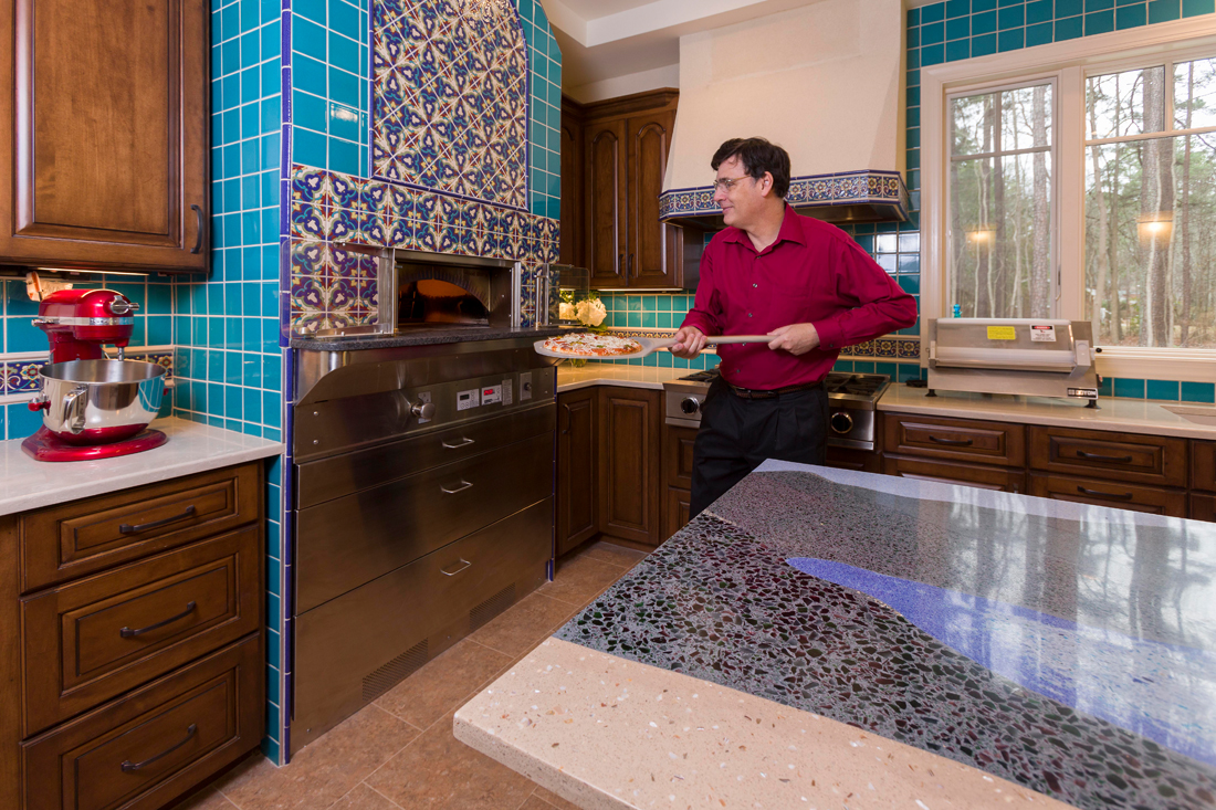 The Toebes' commercial pizza oven is the first to be installed in a local residence, and is surrounded by colorful semi-custom Talavera-style tile, also reflected in the range hood and on a nearby window over one of their wine refrigerators. Coordinating solid color tiles are used in the backsplash.