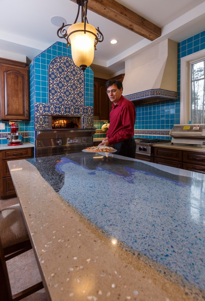 John Toebes demonstrates the home's commercial pizza oven, the first to be installed in a local residence. The oven is surrounded by colorful semi-custom Talavera-style tile, also reflected in the range hood. Coordinating solid color tiles are used in the backsplash.
