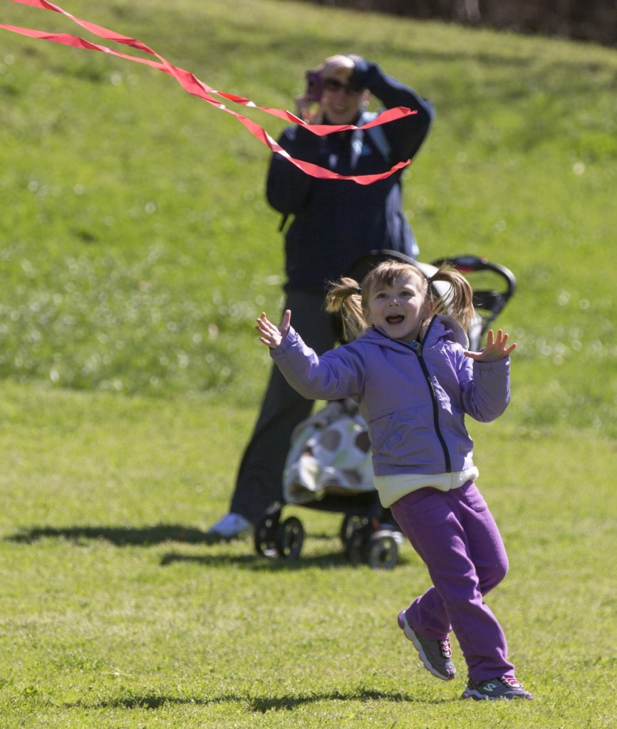 Three-year-old Evie Richardson chases the tail of a kite flown by her father, Chad Richardson of Cary, at the 22nd Annual Kite Festival at Fred G. Metro Bond Park.