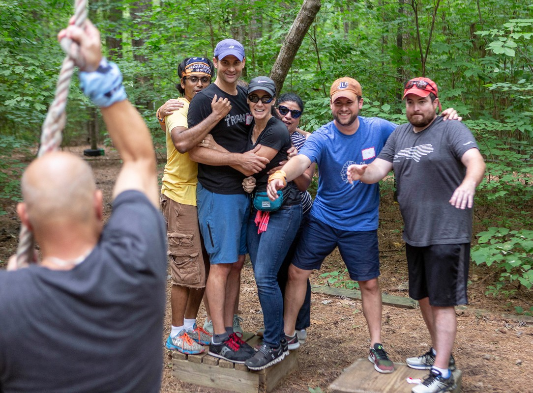 Google Fiber coworkers prepare to catch a teammate swinging toward them at Bond Park's Challenge Course.